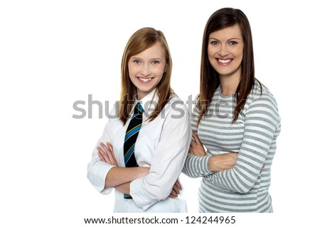 Beautiful mom and daughter posing with confidence, arms folded. - stock photo