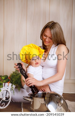 beautiful mom and son in the kitchen - stock photo