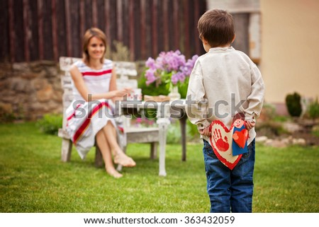 Beautiful mom, having coffee in a backyard, young cute child giving her present and flowers for her birthday. Mother day concept, love, happiness, cozy atmosphere - stock photo
