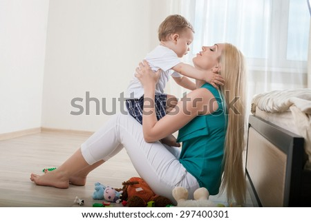 Beautiful mom is hugging her small son with love. They are looking at each other gently. The parent is holding her kid and sitting on floor - stock photo