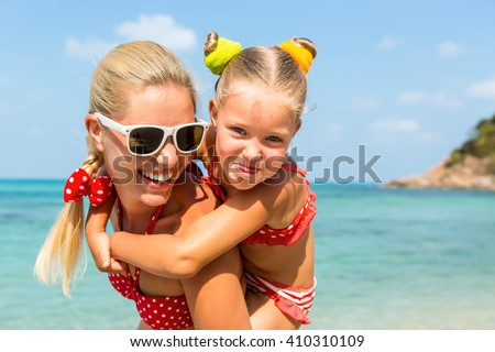 Beautiful mom sunglasses with cute little daughter on her back. Two in red bikini. Woman and little girl smile and looking to camera. Happy family on the sea shore. Happy mothers day. - stock photo