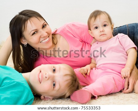 beautiful mom with her children on a carpet - stock photo
