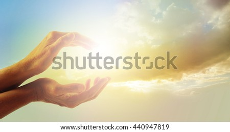 Beautiful moment in Nature - female hands cupped with evening sunlight captured between and beautiful gentle dusk clouds in background - stock photo