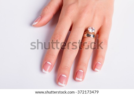 Beautiful moon french manicure. Diamond ring and wedding ring on woman's finger.