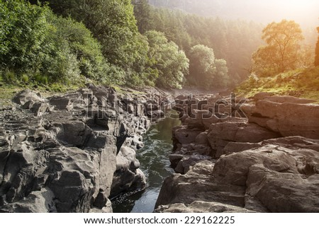 Beautiful morning landscape image of sunlight through trees into canyon creek below - stock photo
