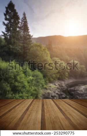 Beautiful morning landscape image of sunlight through trees into canyon creek below with wooden planks floor - stock photo