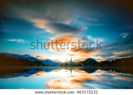 Beautiful morning landscape with snowed up Alpes on the Bled lake in Slovenia. Long exposure image technic with blurred clouds and glossy water