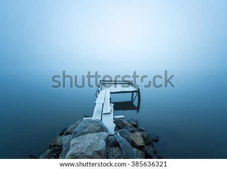 Beautiful morning mist by the lake. Foggy morning. Autumnal frosty coastal river gangway on long exposure. - stock photo