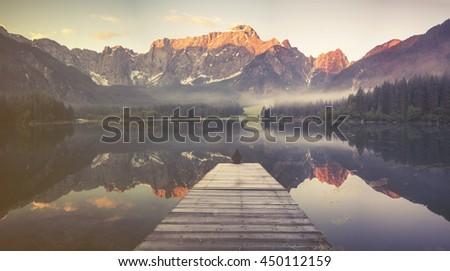 beautiful morning on the alpine lake in Italian Alps,Vintage retro stylized photo of mountain lake - stock photo