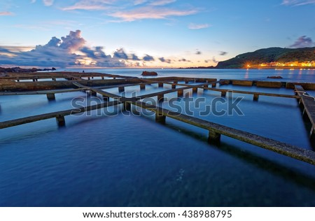 Beautiful morning scenery of a sea ranch ( fish farming ) in northern Taiwan, with peculiar artificial structures of aquaculture fishery and an island on the distant horizon under dramatic dawning sky - stock photo