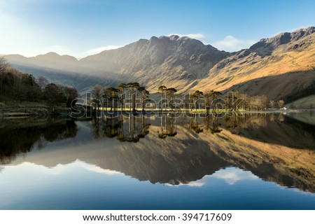 Beautiful morning sunlight shining on Buttermere in the Lake District with mirror like reflections.  - stock photo