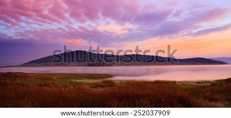 Beautiful morning with rising sun on lake, pink dominant colors  - stock photo