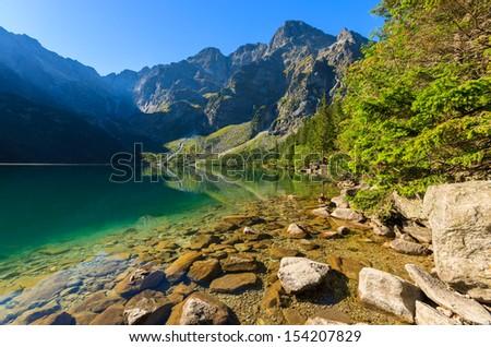 Beautiful Morskie Oko green water alpine lake on sunny day, Tatry Mountains (High Tatras), Poland  - stock photo