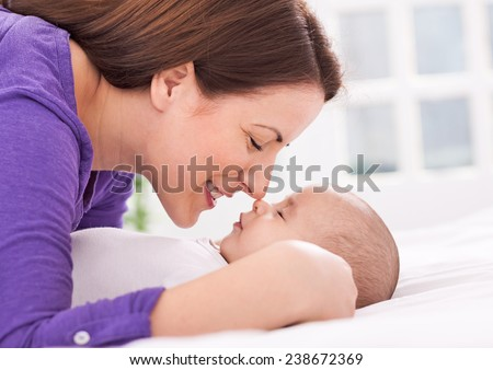 Beautiful mother and baby are gently touching noses - stock photo