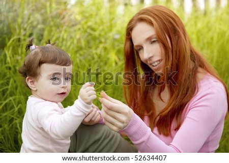 beautiful mother and baby little girl outdoor park garden grass playing - stock photo