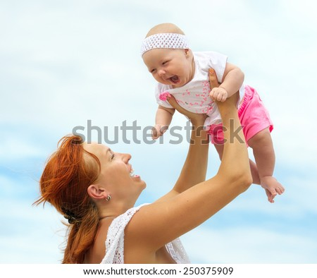 Beautiful Mother And Baby outdoors. Nature. Beauty Mum and her Child playing in beach together. Outdoor Portrait of happy family. Joy. Mom and Baby    - stock photo