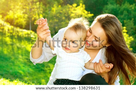 Beautiful Mother And Baby outdoors. Nature. Beauty Mum and her Child playing in Park