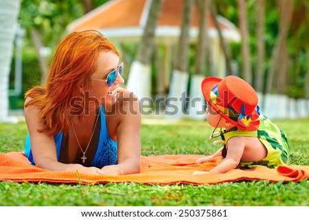 Beautiful Mother And Baby outdoors. Nature. Beauty Mum and her Child playing in Park - stock photo