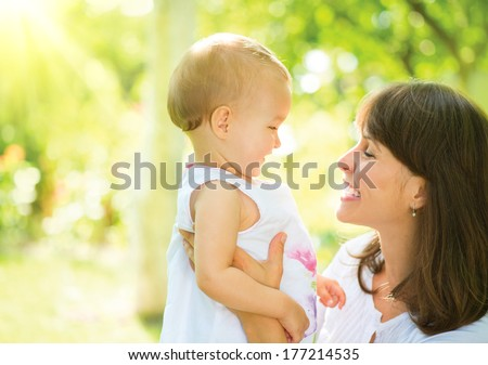 Beautiful Mother And Baby outdoors. Nature. Beauty Mum and her Child playing in Park together. Spring Outdoor Portrait of happy family. Joy. Mom and Baby  - stock photo