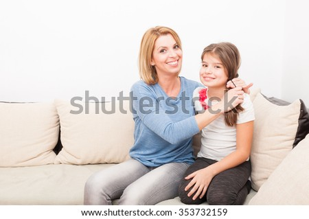 Beautiful mother and daughter at home on the couch or sofa having fun time together