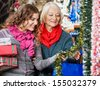 Beautiful mother and daughter buying Christmas decorations in store - stock photo