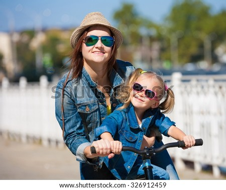Beautiful mother and daughter cyclist, has happy fun cheerful smiling face, yellow t-shirt, blue jeans and hat, sunglasses, sport body. Motion on great bicycle in urban city. Portrait nature.  - stock photo