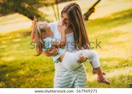 Beautiful mother and daughter having fun at the park in spring day.