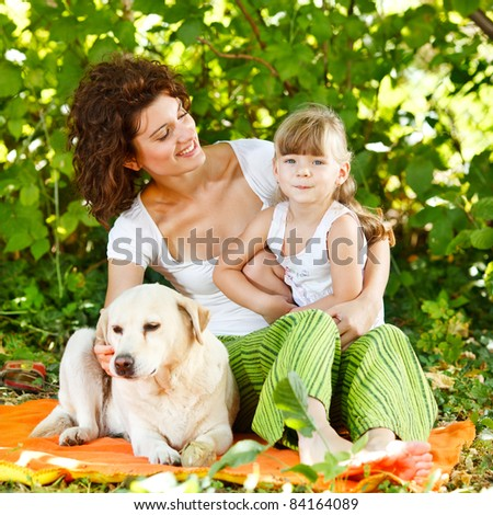 Beautiful mother and daughter relaxing in nature with their dog - stock photo