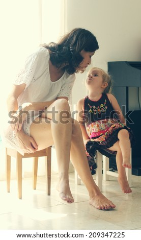 beautiful mother and daughter sitting near the window - stock photo