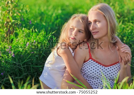 Beautiful mother and daughter sitting on green lush grass meadow in sunset sun beams - stock photo