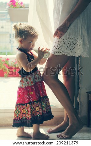 beautiful mother and daughter standing near the window - stock photo
