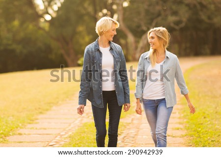 beautiful mother and daughter walking in the forest - stock photo
