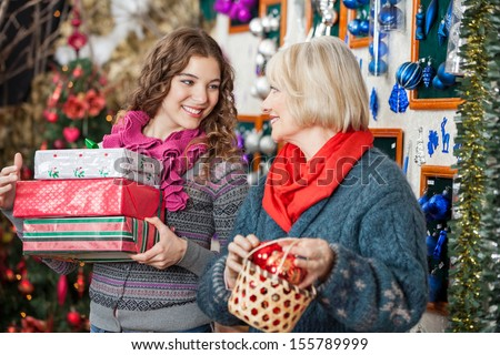 Beautiful mother and daughter with bauble basket and presents in Christmas store