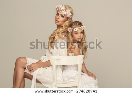 Beautiful mother and daughter with wreath - stock photo