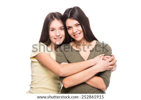 Beautiful mother and her cute daughter smiling and posing on the white background. - stock photo