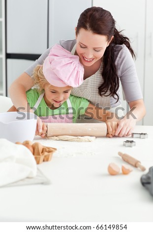 Beautiful mother and her cute daughter using a rolling pin together in the kitchen - stock photo