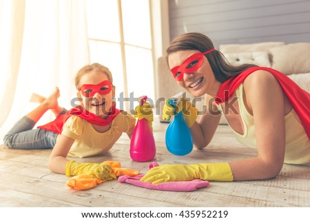 Beautiful mother and her cute little daughter dressed like superheroes are holding sprayer, looking at camera and smiling while cleaning the house - stock photo