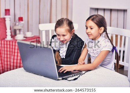 Beautiful mother and her cute teen daughter are using digital tablet while sitting on sofa at home. - stock photo