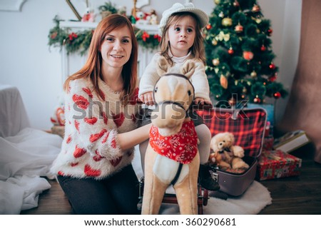Beautiful mother and her daughter who sits on a toy horse - stock photo