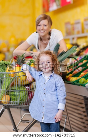Beautiful mother and her little redhead daughter posing with a trolley full of fresh produce in a supermarket