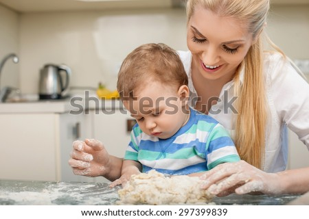 Beautiful mother and her little toddler are doing dough with fun. The woman is looking at her child with love and smiling. They are sitting at the table in the kitchen. Copy space in left side - stock photo