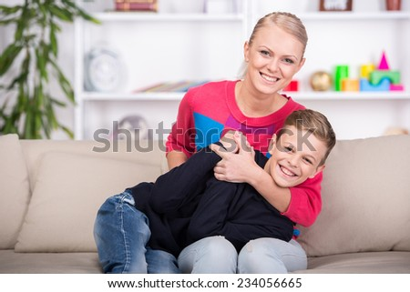 Beautiful mother and her son is sitting on the sofa at home and smiling. - stock photo