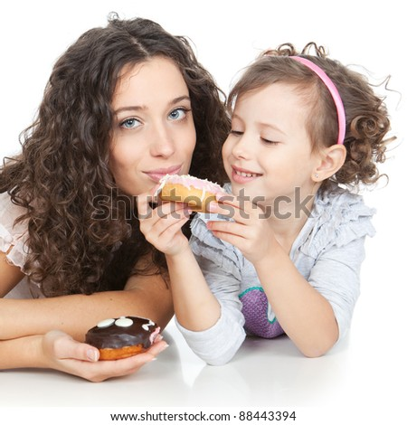 beautiful mother and little daughter eating colorful donuts over white background