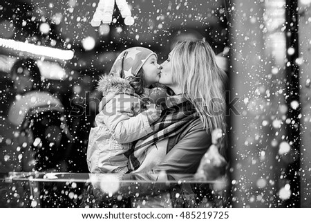 Beautiful mother and little daughter eating crystalized sugared apple on German Christmas market. Happy family in winter clothes with lights on background. Black and white picture.