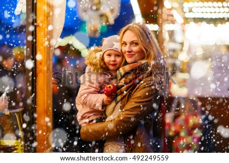 Beautiful mother and little daughter eating crystalized sugared apple on German Christmas market. Happy family in winter clothes with lights on background. Family, tradition, holiday concept