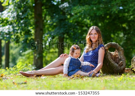 Beautiful mother and little daughter having fun together in summer park