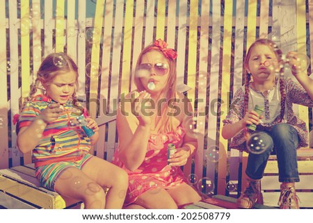 Beautiful mother and little daughters blowing soap bubbles together in summer  - stock photo