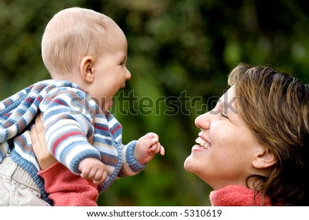 beautiful mother and son looking happy and smiling outdoors - stock photo