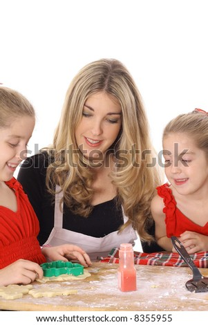 beautiful mother and twin daughters decorating cookies
