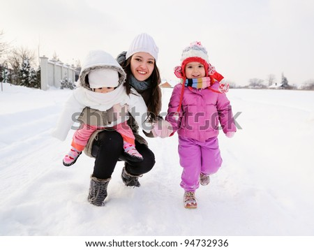 Beautiful mother and two daughters enjoying winter outdoors. They are smiling and playful in the snow. - stock photo